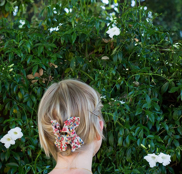 white trumpet flowers, pink floral hair clip in blonde hair