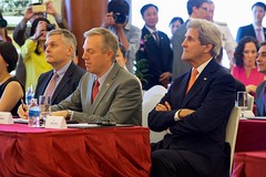 U.S. Secretary of State John Kerry sits between U.S. Ambassdor to Vietnam Ted Osius and Secretary of Ho Chi Minh City Party Committee Dinh La Thang on May 25, 2016, at the Rex Hotel in Ho Chi Minh City, Vietnam, during a ceremony to mark the licensing of the U.S.-supported Fulbright University Vietnam. [State Department photo/ Public Domain]