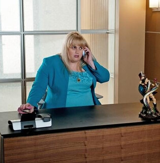 Rebel Wilson at an office desk