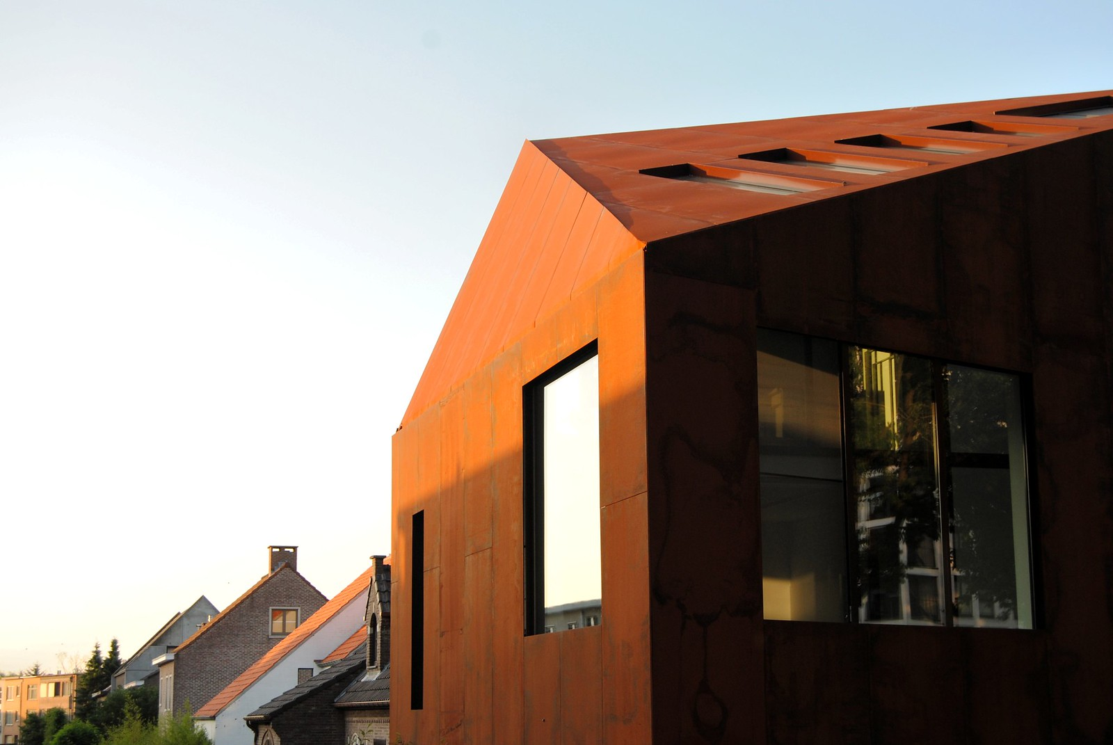 A copper-toned house features contemporary, geometric architecture.