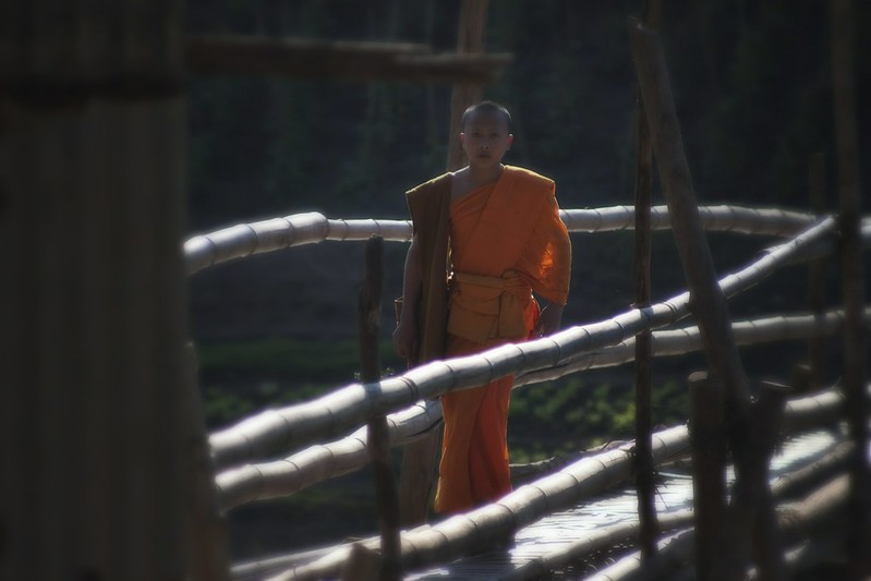 A Laotian Novice Monk Crosses A Bridge