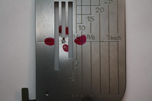 This is not what a needle plate should look like - the repairman marked it up with the nail polish to draw attention to the needle hole, where the damage is