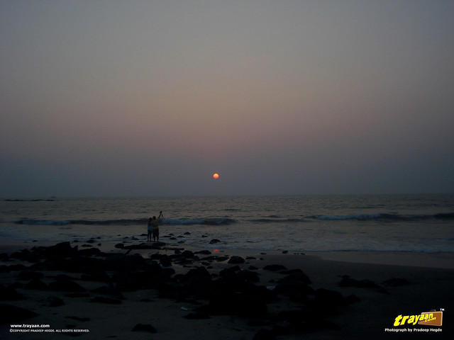 A couple, photographing the sunset at Tannirbavi Beach, Mangalore, Dakshina Kannada, Karnataka, India