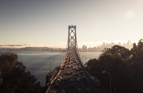 sanfrancisco california road city bridge sunset sea sky urban usa cloud building car sunshine weather fog skyline architecture sailboat harbor cityscape crossing traffic unitedstates streetlamp landmark structure baybridge dreamy elevated toned across yerbabuenaisland pedestalshot