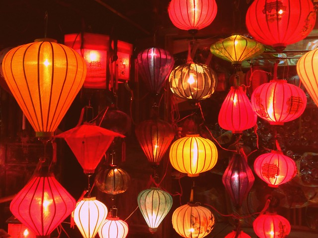 Silk lanterns glow in a market at night