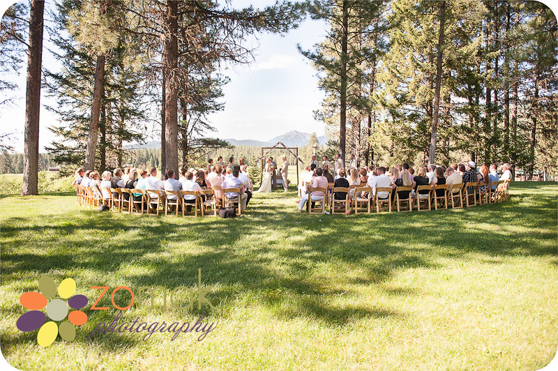 Allison and Zach celebrate their wedding in the shade of giant pine trees at the Double Arrow resort in Seeley Lake Montana on a beautiful sunny day