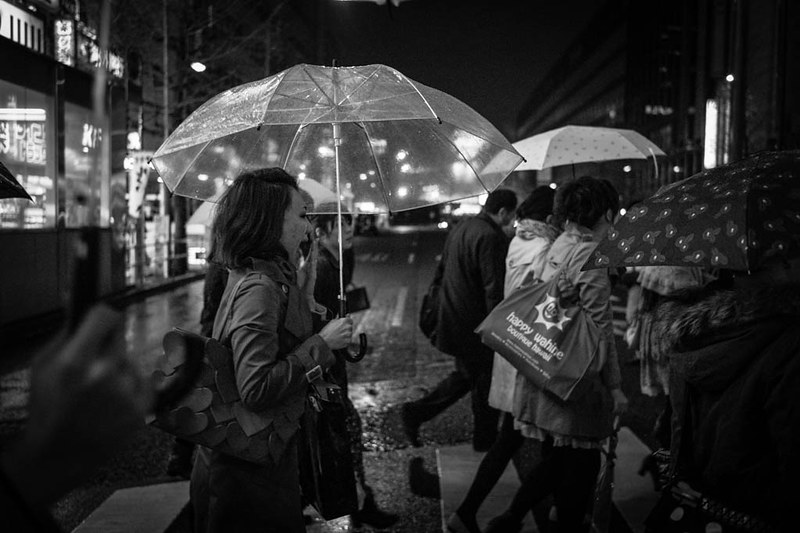 A woman  with a transparent umbrella yawning as she crosses a road in Shinjuku.