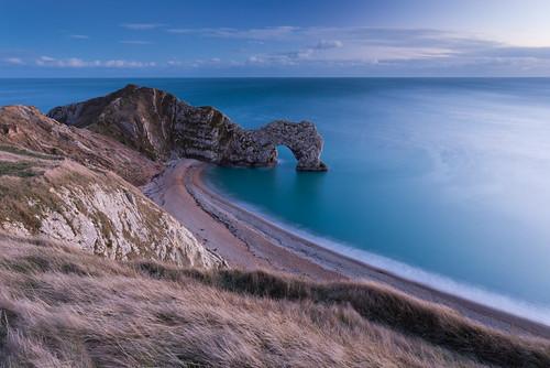 blue sunset sea england cloud seascape colour rock canon landscape photography coast arch jake unitedkingdom dusk shoreline cliffs dorset pike durdledoor westlulworth
