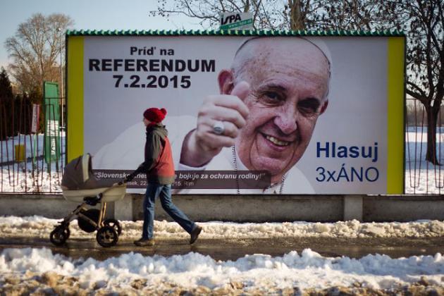 AFP/AFP/Archivos - Una mujer pasa en frente a una valla con el retrato del Papa Francisco, en Bratislava el 3 de febrero de 2015. La leyenda instando a las personas a votar en el referéndum para mantener o prohibir el matrimonio homosexual en Eslovaquia