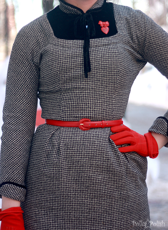 Detail of a black and white basketweave wool dress styled with red gloves, belt, and brooch
