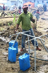 A Ugandan Red Cross volunteer collecting water, Bubukwanga transit center