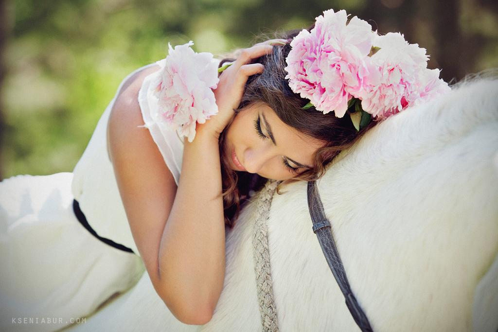 Прогулочная фотосессия девушки с белой лошадью и пионами