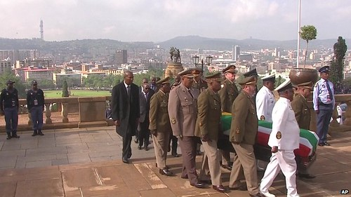 Military officers carry the coffin of the former President Nelson Mandela to the Union building in Pretoria. He will lay in state for three days. by Pan-African News Wire File Photos