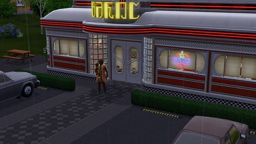 A hot dog and his child stand in the rain outside the diner