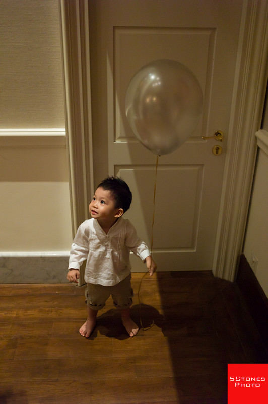 Kid with balloon standing in the light.