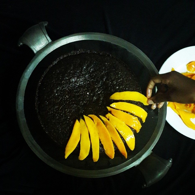 The makings of a cake: my regular chocolate cake topped with sliced mangoes glazed with a simple syrup of sugar and water and the tiniest bit of the bitter lime marmalade.  Hands by @sunshine_3500  #baking #copiedideasfromekohotel #learning
