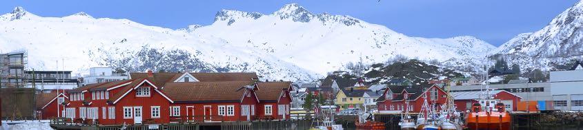 Rorbuers (Rorbürs), norwegische Fischerhütten, im Hafen von Svolvaer (Svolvär), dahinter Skitourenberge auf den Lofoten. Foto: Günther Härter.