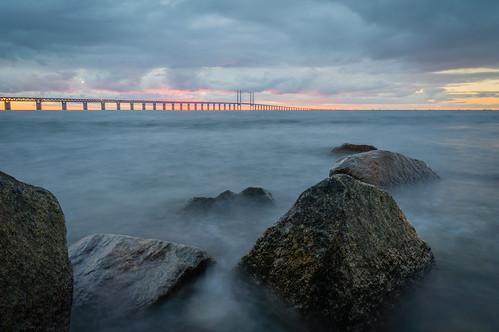 longexposure bridge pink sunset water yellow night clouds grey rocks purple cloudy sweden stones malmö theøresundbridge skånecounty