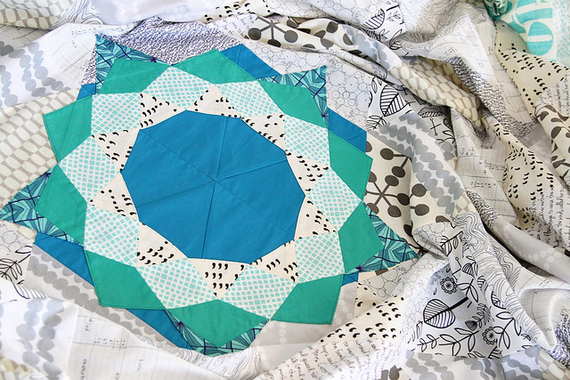 An english paper pieced star ring sewn to a quilt of low volume triangles
