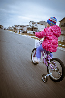 A child riding away from the camera on a pink bicycle with training wheels and a white wicker basket