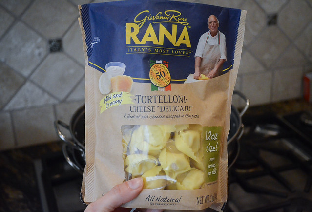 A hand holds a bag of Rana Cheese Tortelloni.