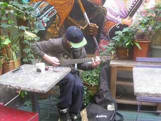 Patron practicing on an unplugged electric guitar in the back courtyard of Cafe International, Haight Street west of Fillmore, San Francisco, CA