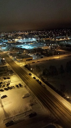 Night lighting midwinter from 15 stories above 6th Ave, parking lot, cemetery, lights, Anchorage, Alaska, USA by Wonderlane