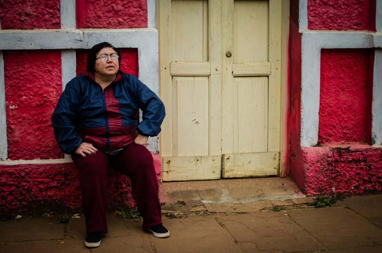 Una señora observa sentada frente a su casa el desfile de caballerías que se llevó a cabo el domingo 26 de junio en el centro de la ciudad de San Juan, departamento de Misiones. (Elton Núñez)