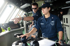 Cmdr. Pat Thien, left, commanding officer of the littoral combat ship USS Freedom (LCS 1), guides Mass Communication Specialist 3rd Class Karolina Oseguera as she pilots the ship during a man overboard drill in the South China Sea, Aug. 13. (U.S. Navy photo by Chief (Select) Mass Communication Specialist Cassandra Thompson)