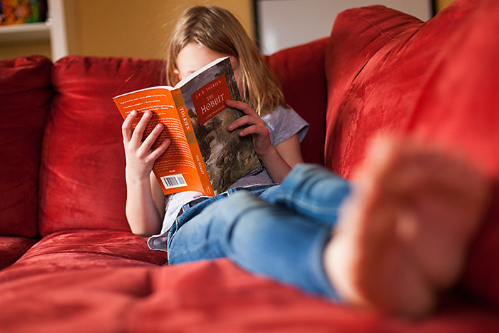 A 7 Year old reading The Hobbit on a red couch