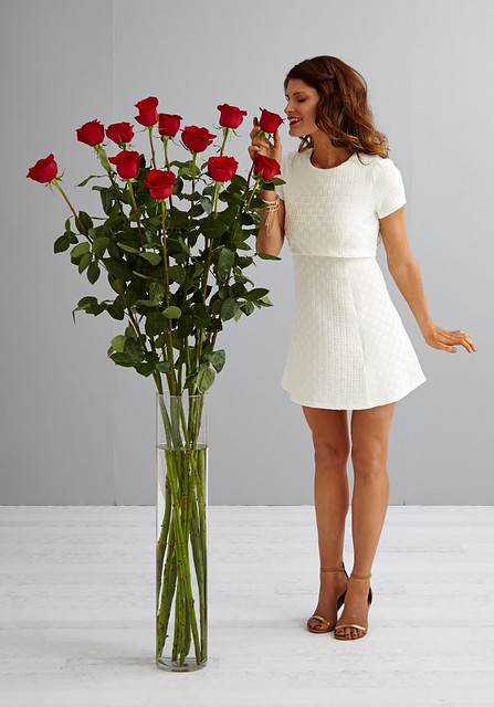 Woman In White Dress With Giant Five Foot Tall Red Roses