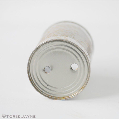 Drill holes in base of can