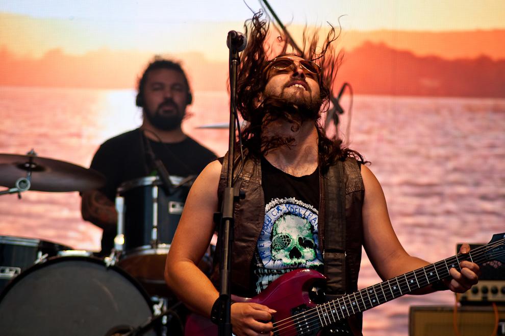 """El vocalista de """"Salamandra"""", Javier Zacher, agita la cabeza mientras interpretan las canciones que encantaron al público, llevando en alto el emblema de su ciudad natal, el Lago Ypacaraí, de fondo. (Elton Núñez)"""