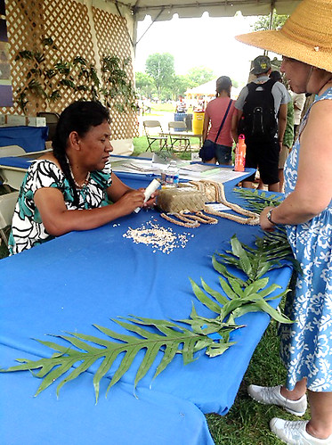 <p>Niihau lei maker Kanani Beniamina demonstrates the art of shell lei crafting to Smithsonian Folklife Festival visitors at the University of Hawaii exhibit.</p>