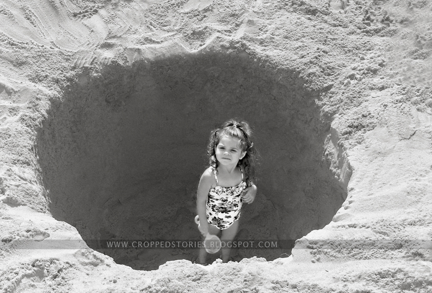 toddler in sand hole at beach