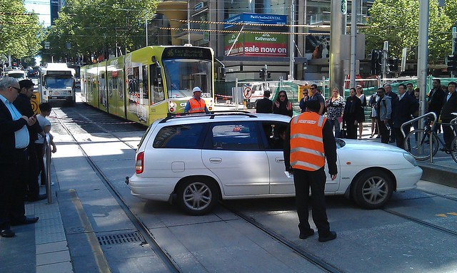 Car making a 3-point turn between tram platforms, Bourke Street Mall