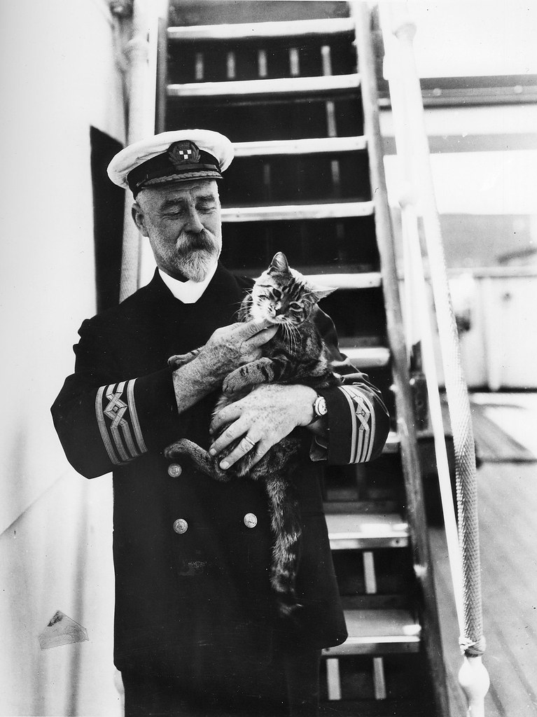[Captain A. J. Hailey in uniform with a cat on the first C.P. R.M.S. Empress of Canada]