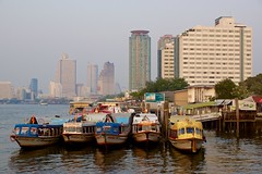 Bangkok skyline in the evening with express boats seen from Asiatique - The riverfront by the Chao Phraya river in Bangkok, Thailand
