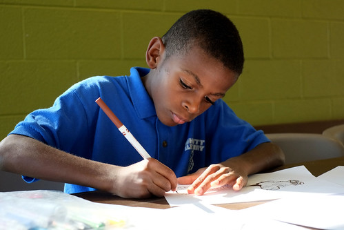 Child doing homework at a Community Center where Kids Café is held. Image provided by Feeding America.