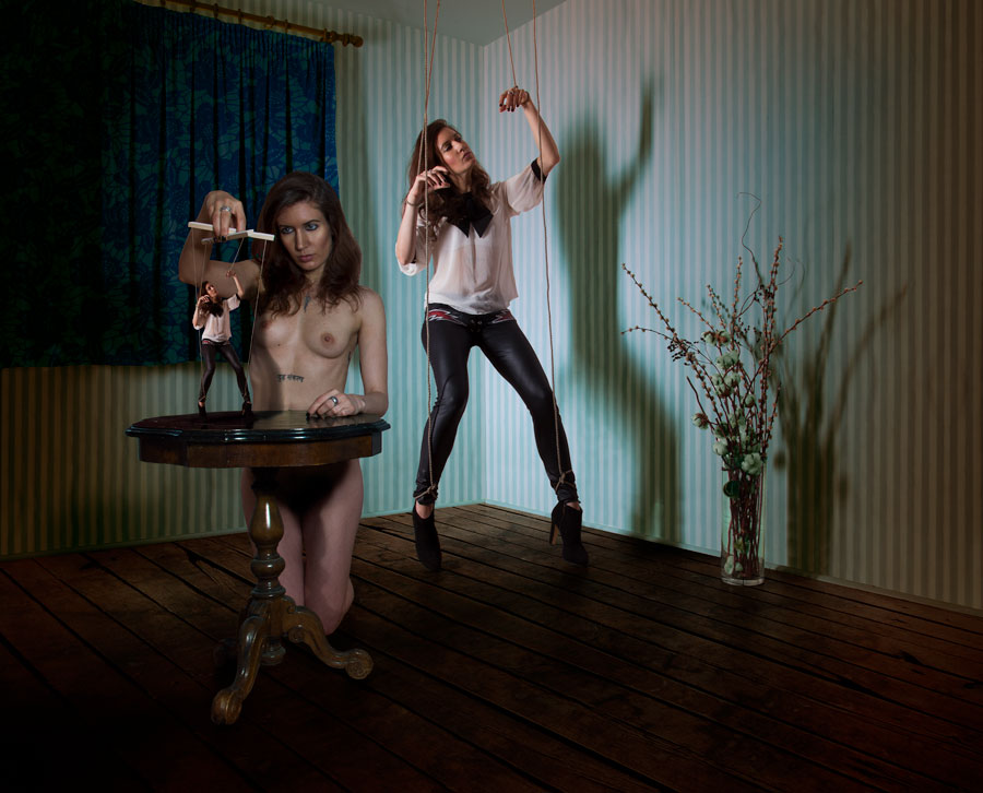 Photography by Gestalta. A woman plays with a puppet of herself.