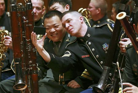 Musicians from the military bands of China's People's Liberation Army and the U.S. Army take photos during a rehearsal for their joint concert at the National Centre for the Performing Arts in Beijing, in this October 29, 2012 file photo. Credit: Reuters/China Daily/Files