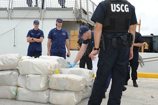 A Coast Guard Cutter Thetis crew member stacks bales of interdicted contraband on the pier at Coast Guard Sector Key West after offloading them from the Coast Guard Cutter Thetis, Sept. 11, 2013. The cutter Thetis returned to home port on Sept. 11, 2013, to offload more than 6,000 pounds of marijuana stemming from two different Caribbean Sea interdictions.