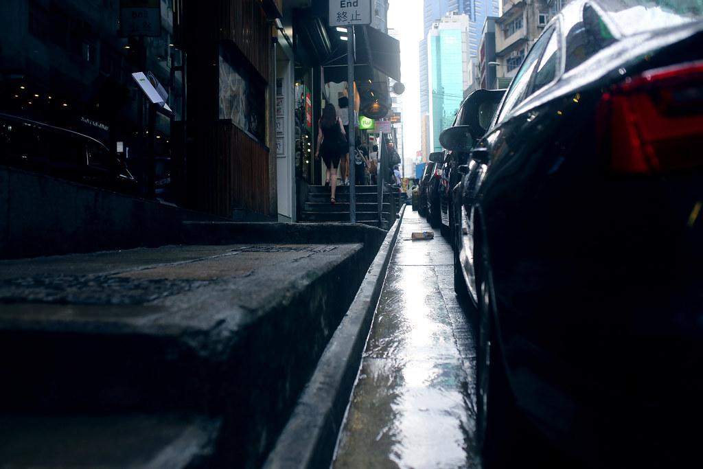 Street Hong Kong / Sigma 35mm / Canon 6D 香港下起雨了,稍微不那麼熱,這樣就可以拍雨天的場景。  這是一個意義不明的對焦,我是對在路面上一個包裹,而不是正在上階梯的女士。  Canon 6D Sigma 35mm F1.4 DG HSM Art IMG_1120 Photo by Toomore