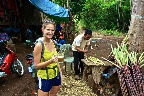 Lina enjoying a drink pressed from raw sugar cane. Man in background, chopping up more sugar cane.