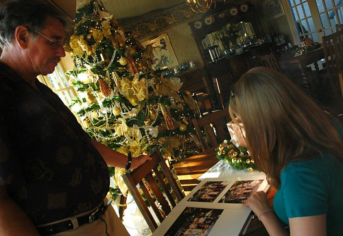 Ever thoughtful, co-owner Terry Baldwin watches bride-to-be Jessie look through wedding albums for ideas, under a yellow and gold Christmas tree, Mill Rose Inn, Half Moon Bay, California, USA by Wonderlane