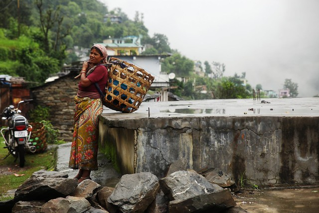 A woman stands by the road in Patyuon village, 20 km from Guptkashi town in India's Himalayan state of Uttarakhand on July 18, 2013. Stranded villagers say there has been no electricity and compensation for their damaged homes and farms, adding that they need roads and bridges to be repaired after floods and landslides devastated the area on June 16 and 17. Credit: Nita Bhalla/Thomson Reuters Foundation