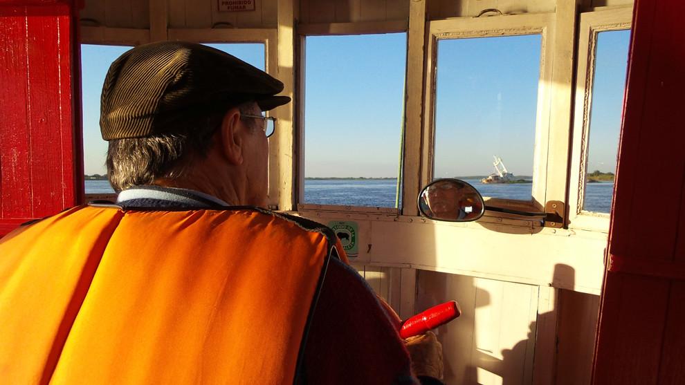 El capitán dirige la pequeña embarcación rumbo a Chaco´i a través del Río Paraguay, al frente se observa un barco encallado. Los botes ofrecen el servicio varias veces al día en una travesía que demora unos 20 minutos. (Tetsu Espósito).