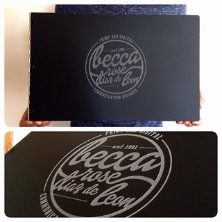 Custom graphic design portfolio book in matte black acrylic with engraving treatment
