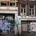 Old house-fronts in Amsterdam city with graffiti tags, photo in 2014