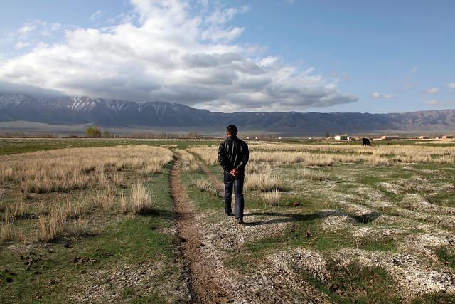A man in Barkol grassland バルクル、草原を歩く男性